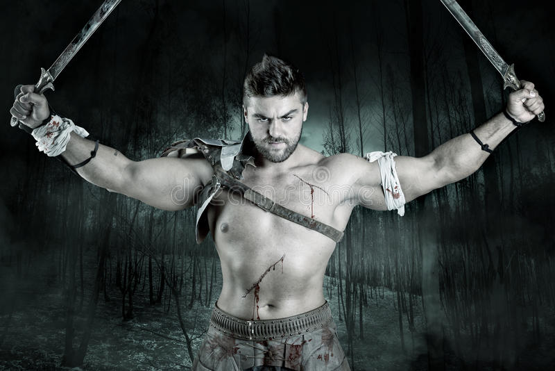 Gladiator/Warrior. Ancient warrior or Gladiator ready to fight in a dark forest royalty free stock photo
