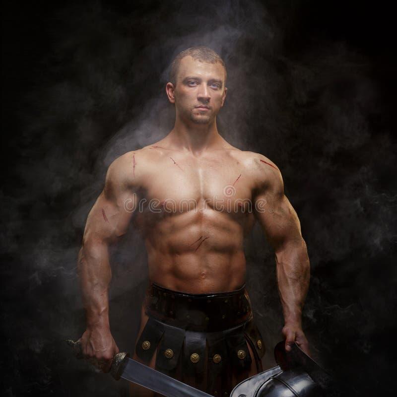 Gladiatore che sta in un fumo in casco e con la spada fotografia stock libera da diritti