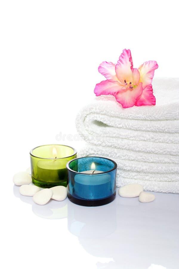 Gladiola, handdoek, kaarsen en rivierstenen stock foto