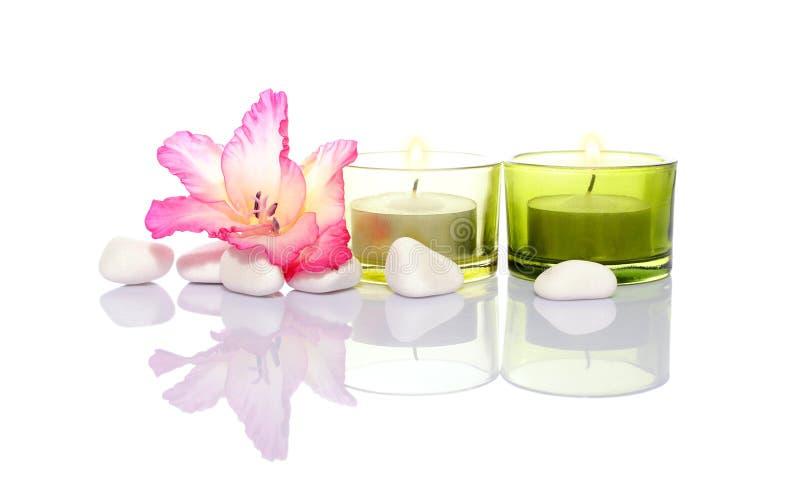Gladiola, kaarsen en rivierstenen royalty-vrije stock afbeelding