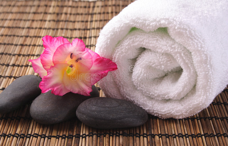 Gladiola, seixos pretos e toalha branca imagem de stock