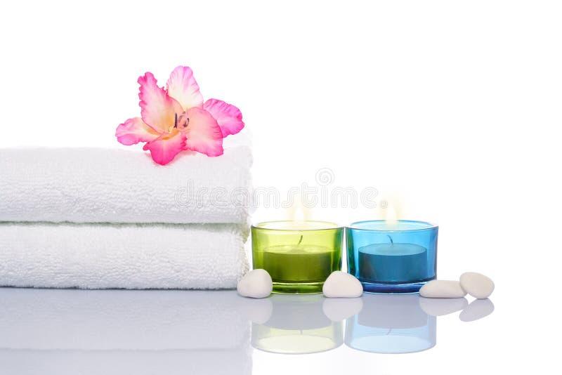 Gladiola, velas, toalha e pedras brancas fotografia de stock royalty free