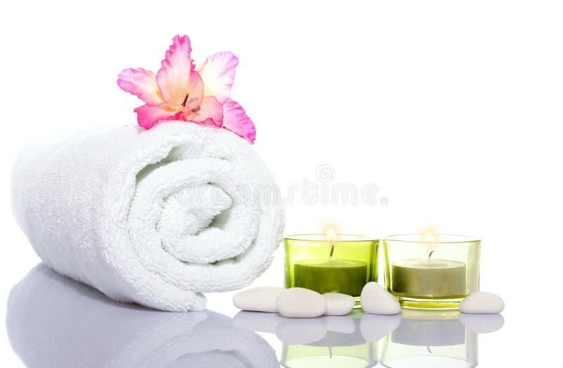 Gladiola, weißes Tuch, Kerzen und Steine des weißen Flusses stockfotos