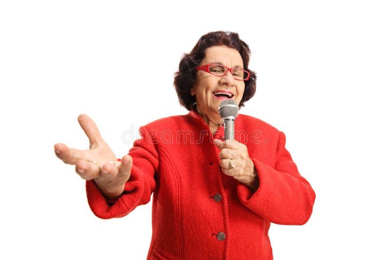Gladlynt äldre dam som sjunger på en mikrofon och tycker om royaltyfria bilder