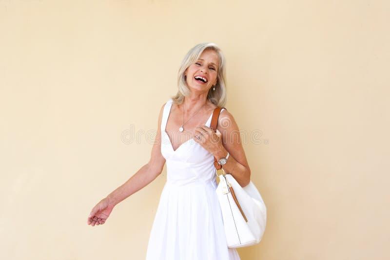 Gladlynt äldre kvinna i sommarklänning arkivbild