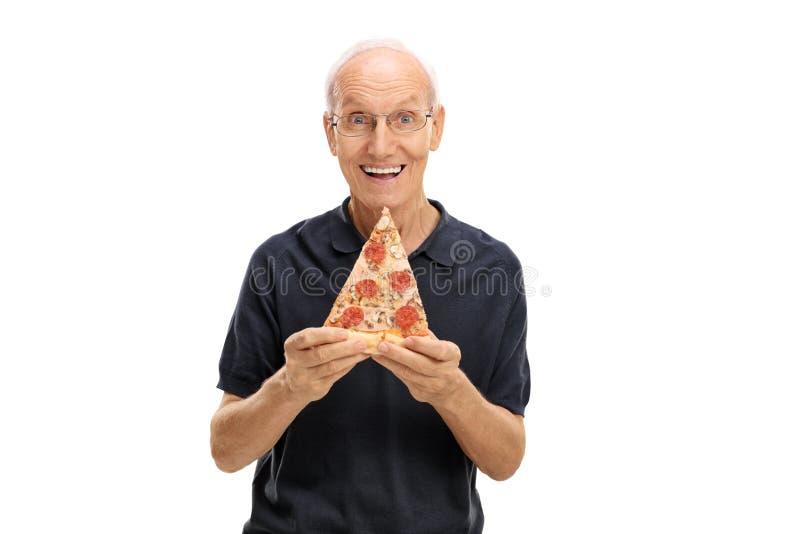 Gladlynt äldre man som rymmer en skiva av pizza royaltyfri fotografi