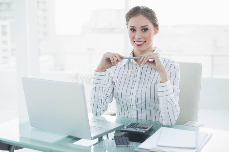 Gladlynt älskvärt affärskvinnasammanträde på hennes skrivbord som rymmer en blyertspenna royaltyfri foto
