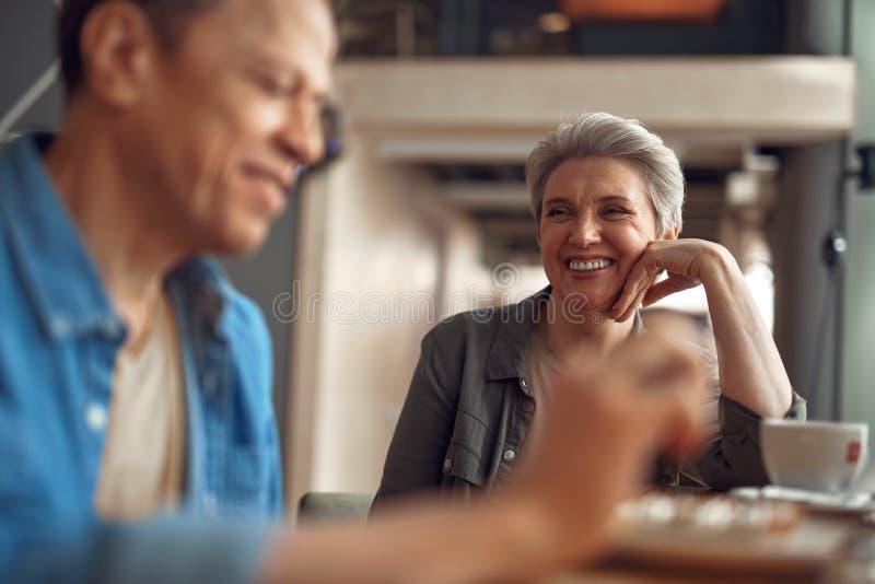 Gladlynt åldrig dam som tycker om möte i kafé arkivfoton