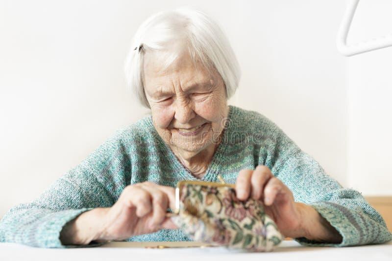 Gladlynt åldring 96 år gammal kvinna som hemma som sitter på tabellen är lycklig med hennes pensionbesparingar i hennes plånbok,  royaltyfri fotografi