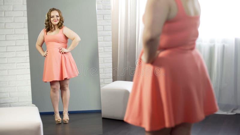 Gladlynt överviktig ung dam som ler på hennes reflexion, kropppositivity arkivfoto