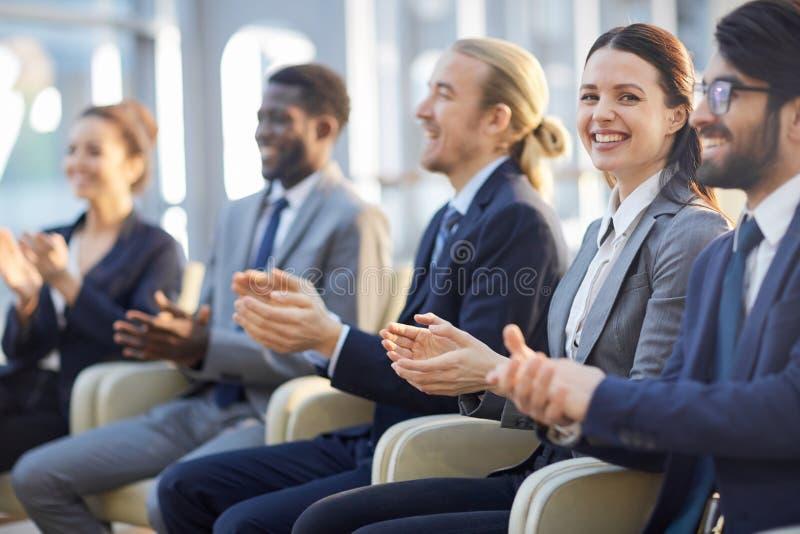 Gladlynt affärsfolk som applåderar i åhörare arkivbilder