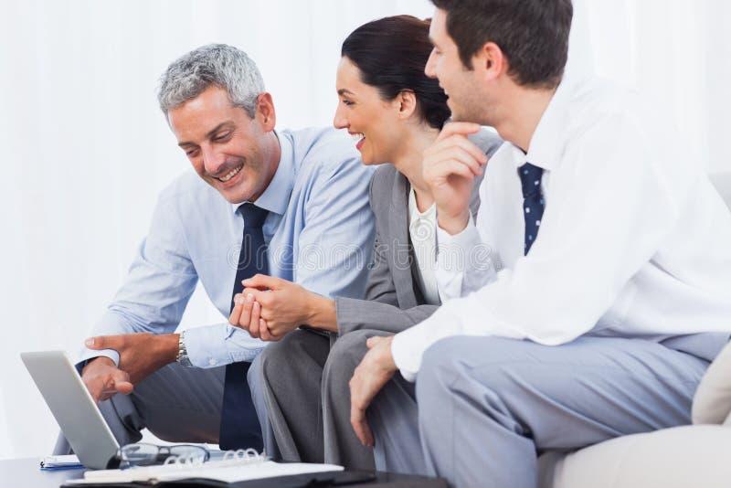 Gladlynt affärsfolk som arbetar med deras bärbar dator på soffan royaltyfri bild