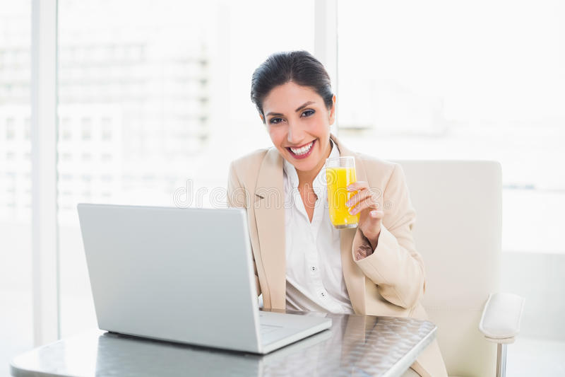 Gladlynt affärskvinna med bärbara datorn och exponeringsglas av orange fruktsaft på royaltyfri fotografi