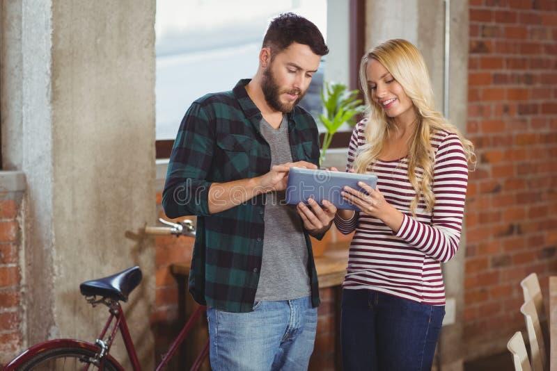 Gladlynt affärskvinna med kollegan som använder den digitala minnestavlan arkivfoto