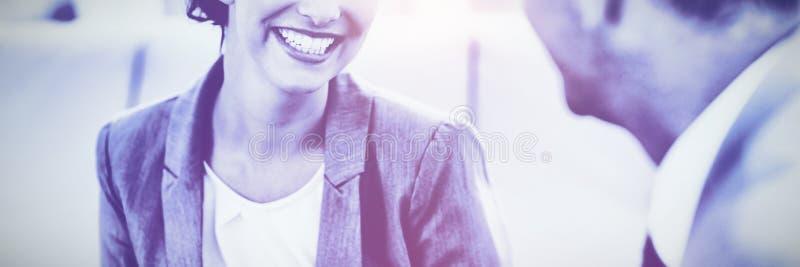 Gladlynt affärskvinna som lyssnar till hennes jobbarkompissamtal fotografering för bildbyråer