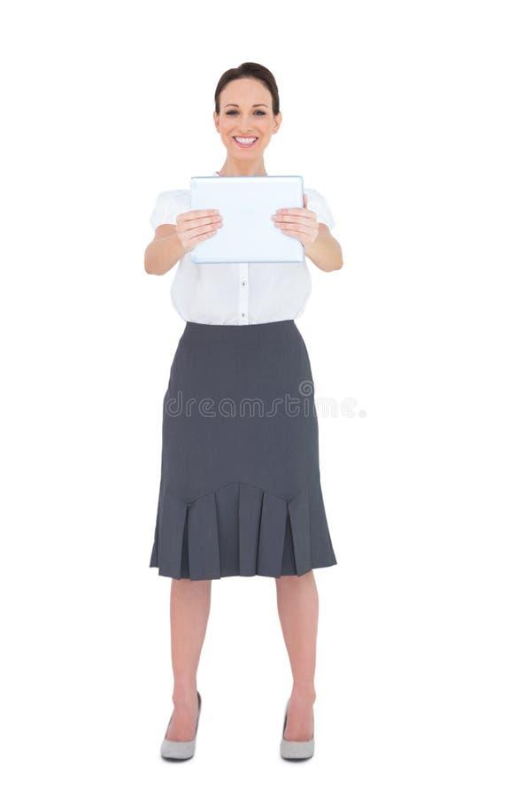 Gladlynt affärskvinna som rymmer hennes minnestavlaPC royaltyfria foton