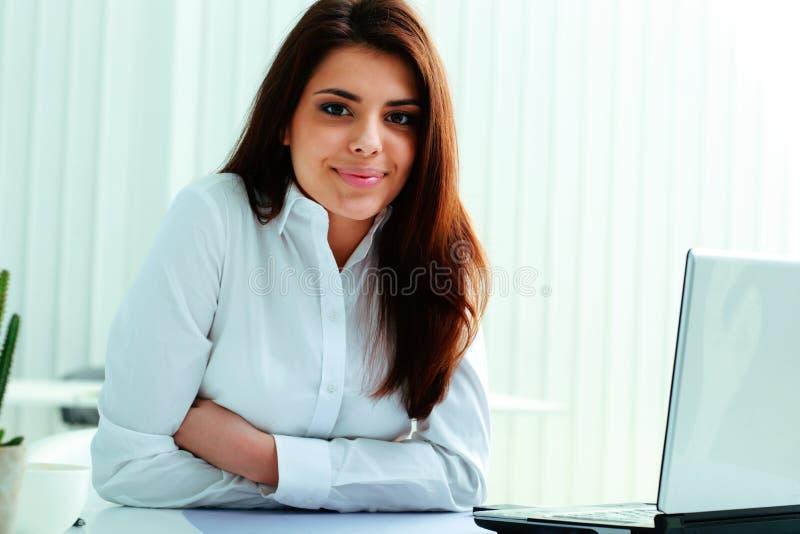 Gladlynt affärskvinnasammanträde på tabellen på hennes arbetsplats arkivfoto