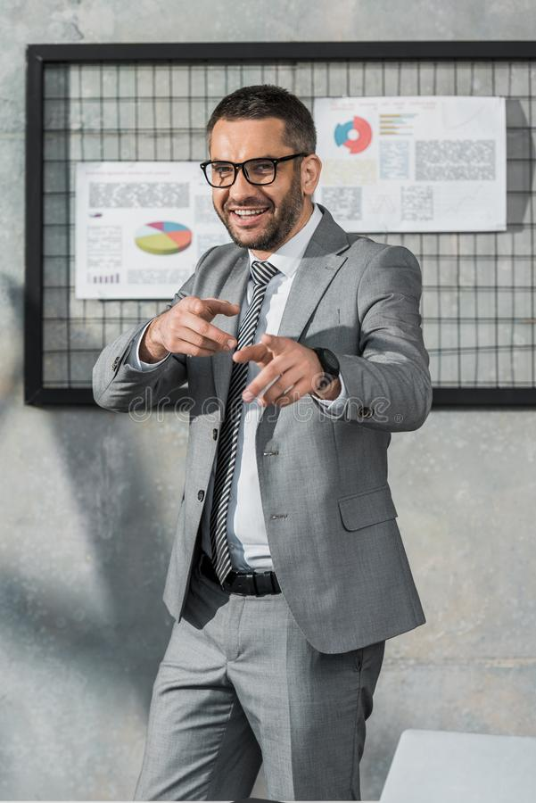 gladlynt affärsman i dräkt och glasögon som pekar med fingrar och ler på kameran arkivfoto
