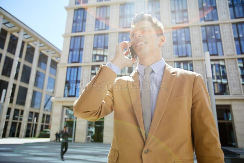 Gladlynt affärsman på telefonen arkivfoton