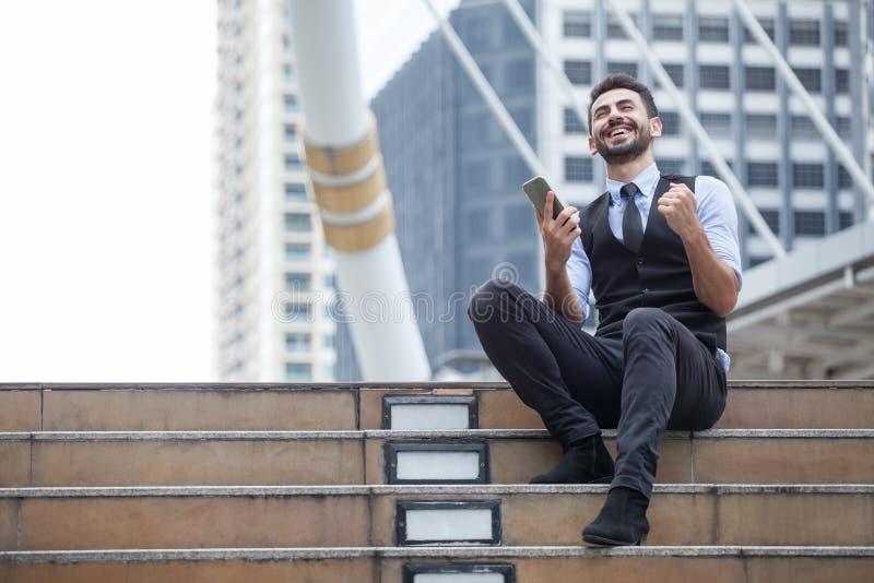 Gladlynt affärsman som firar framgång med mobiltelefonen som utomhus sitter på trappan i stads- stad och att se upp, goda nyheter royaltyfria bilder