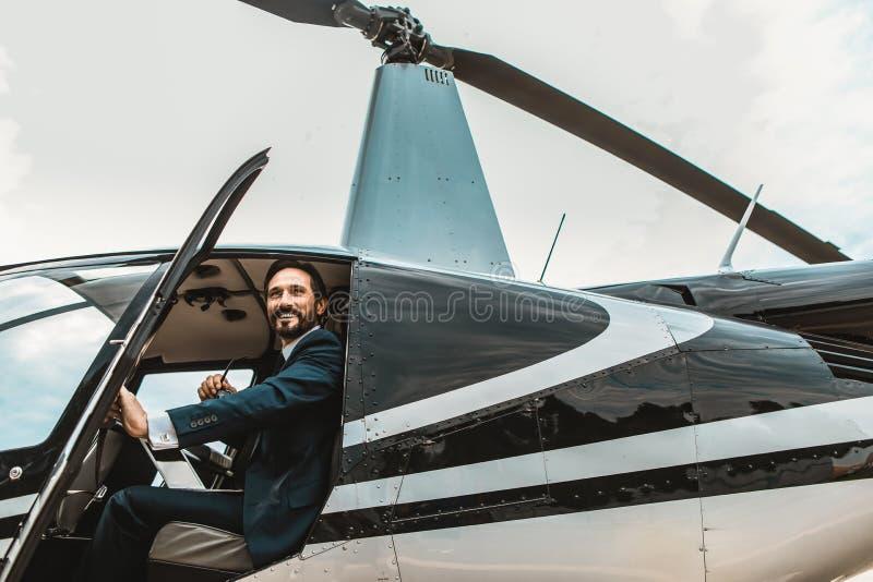 Gladlynt affärsman som ler, medan öppna helikopterdörrarna arkivfoton