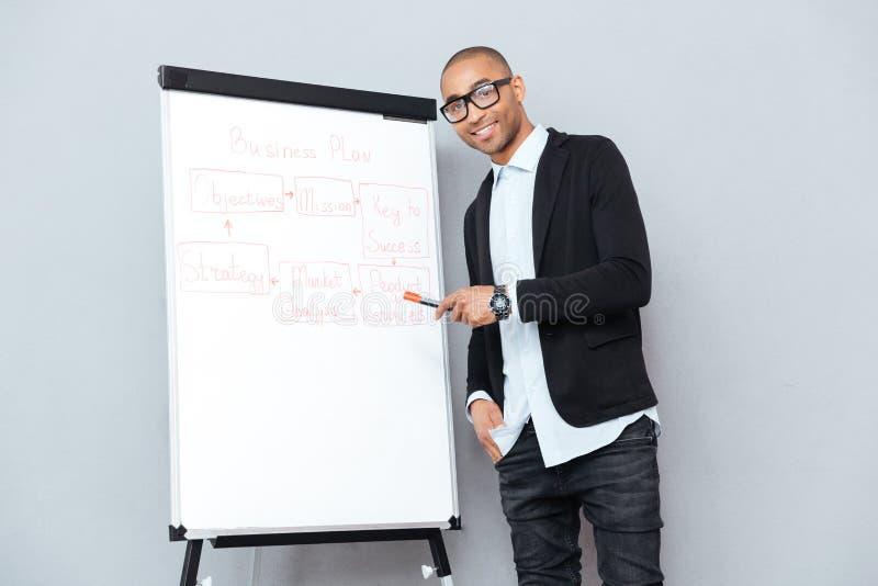 Gladlynt afrikansk affärsman som använder flipchart och pekar på affärsplan arkivfoton