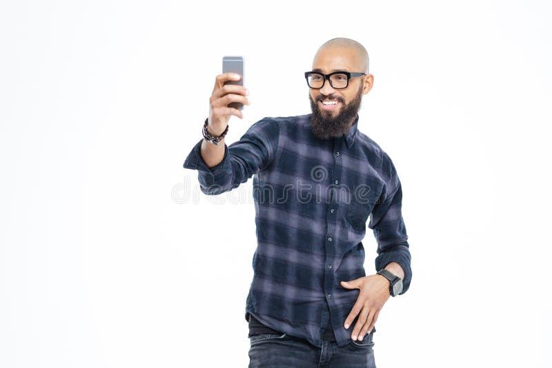 Gladlynt afrikansk amerikanman med skägget som ler och tar selfie royaltyfri bild