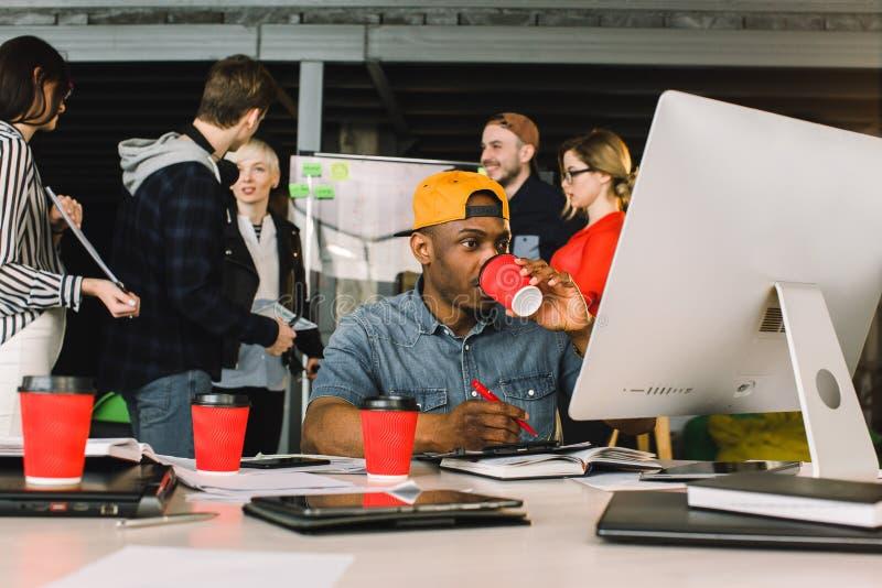 Gladlynt afrikansk man som dricker kaffe och arbetar på datoren, medan sitta på tabellen i modernt kontorsställe hans royaltyfria bilder