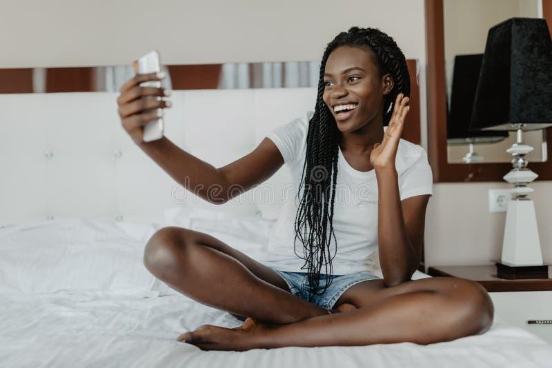 Gladlynt afro amerikansk flicka för blandat lopp som har video pratstund med vänner som använder bärbar datorkameran, medan ligga royaltyfri foto
