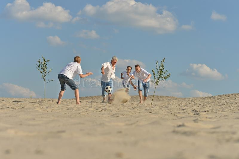 Gladlynt aktiv familj som spelar fotboll royaltyfri fotografi