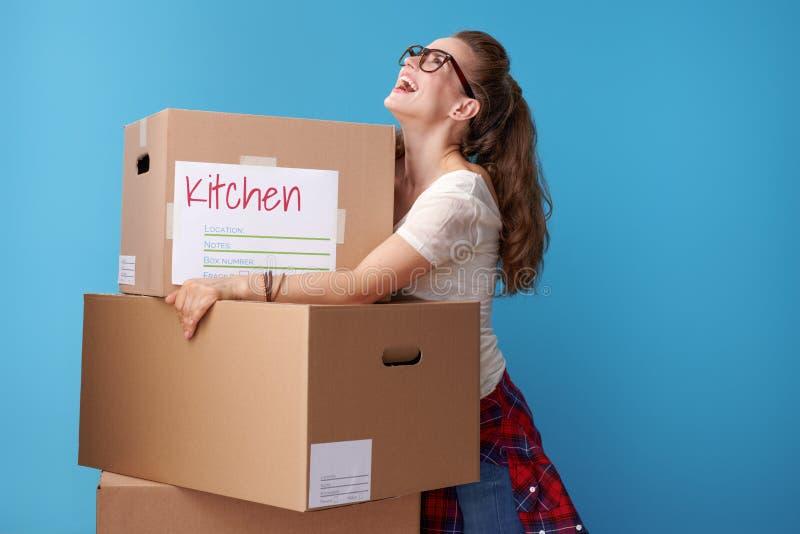 Gladlynt aktiv kvinna som omfamnar kartonger på blått arkivbild