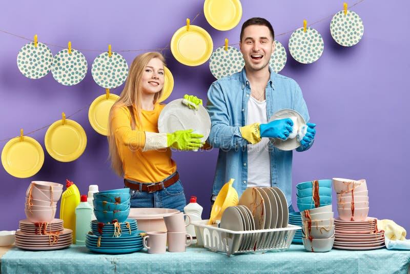 Gladlynt angenäm man och kvinna som tvättar plattorna efter parti royaltyfri bild