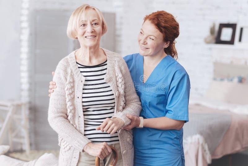 Gladlynt anhörigvårdare som hjälper hennes äldre patient att stå upp arkivbilder