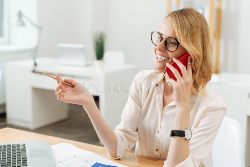 Gladlynt arkitekt som tycker om konversation på telefonen på arbete arkivbilder