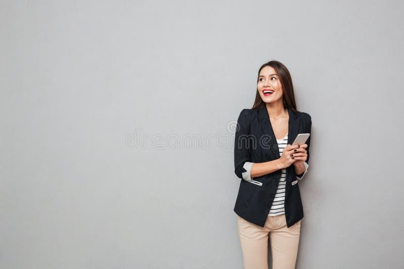 Gladlynt asiatisk hållande smartphone för affärskvinna och se bort royaltyfri bild