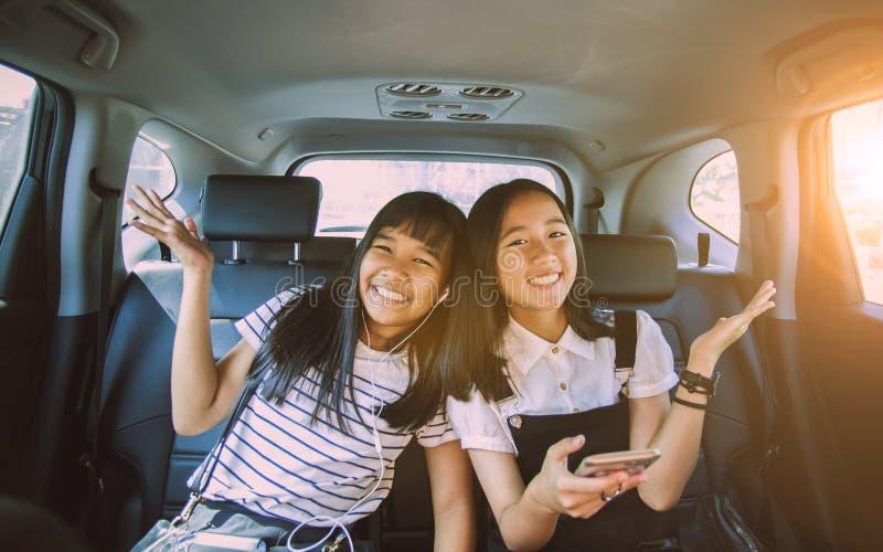 Gladlynt asiatisk tonåringlyckasinnesrörelse som sitter i passagerarebil fotografering för bildbyråer