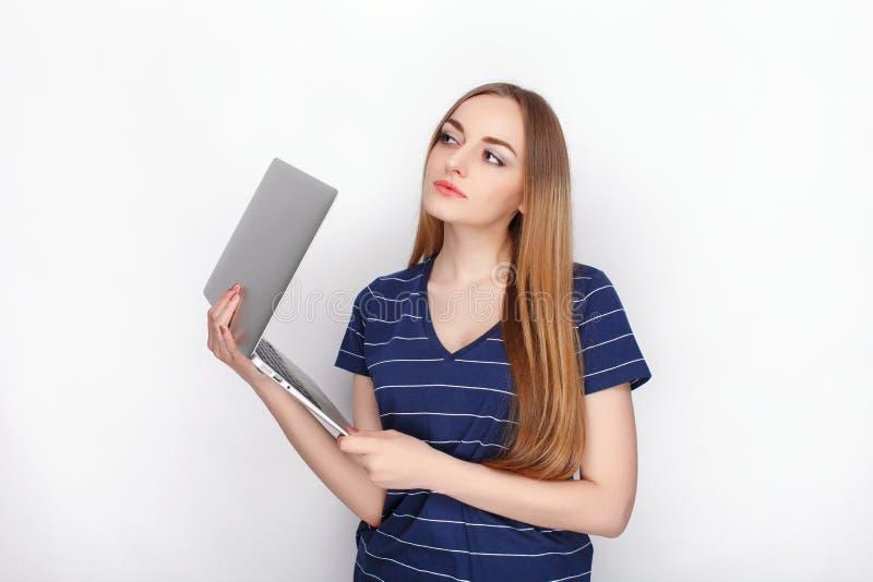 Gladlynt attraktiv caucasian blond kvinna med att använda den slanka eleganta anteckningsbokdatoren som isoleras på en vit bakgru royaltyfria bilder
