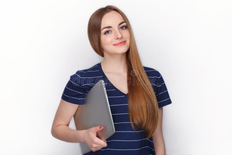 Gladlynt attraktiv caucasian blond kvinna med att använda den slanka eleganta anteckningsbokdatoren som isoleras på en vit bakgru royaltyfri fotografi