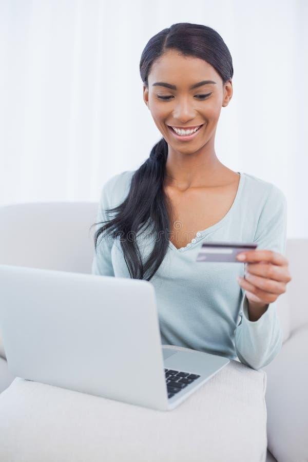 Gladlynt attraktiv kvinna som använder hennes bärbar dator för att köpa direktanslutet royaltyfri foto