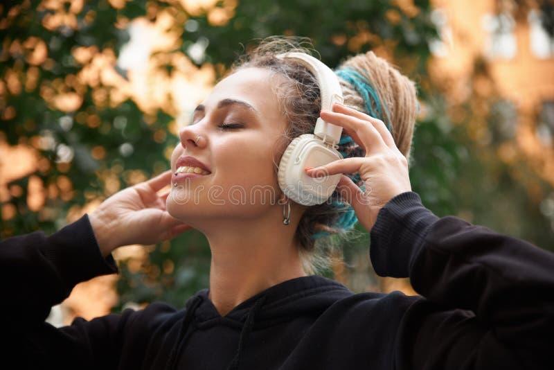 Gladlynt attraktiv ung flicka i hoodie och kulöra dreadlocks arkivbild