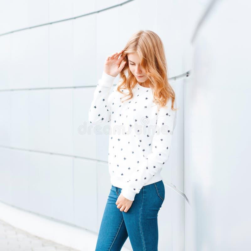 Gladlynt attraktiv ung kvinna med en trendig frisyr i en vit tröja i trendig jeans för tappning nära den moderna väggen royaltyfri foto
