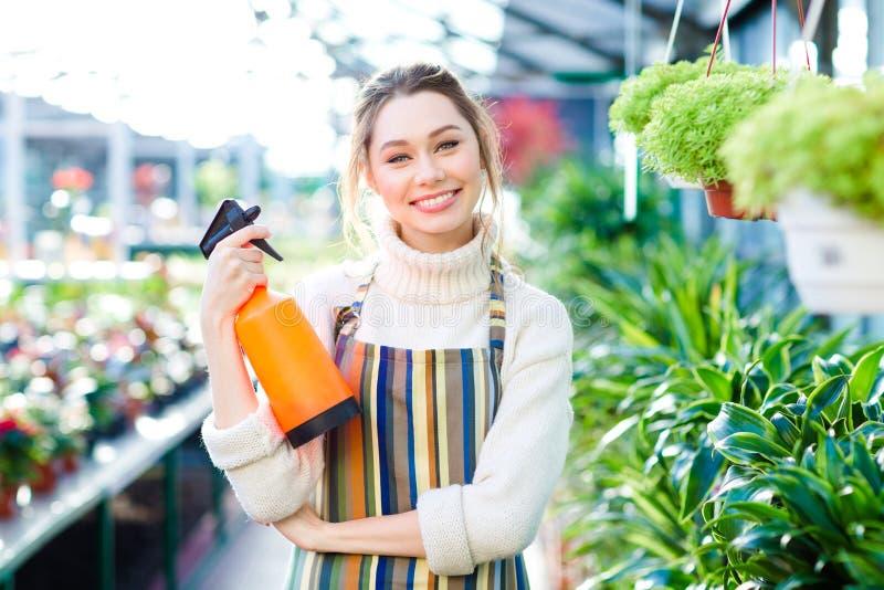 Gladlynt attraktivt kvinnaträdgårdsmästareanseende i orangeri med vattenpulverizeren royaltyfri fotografi