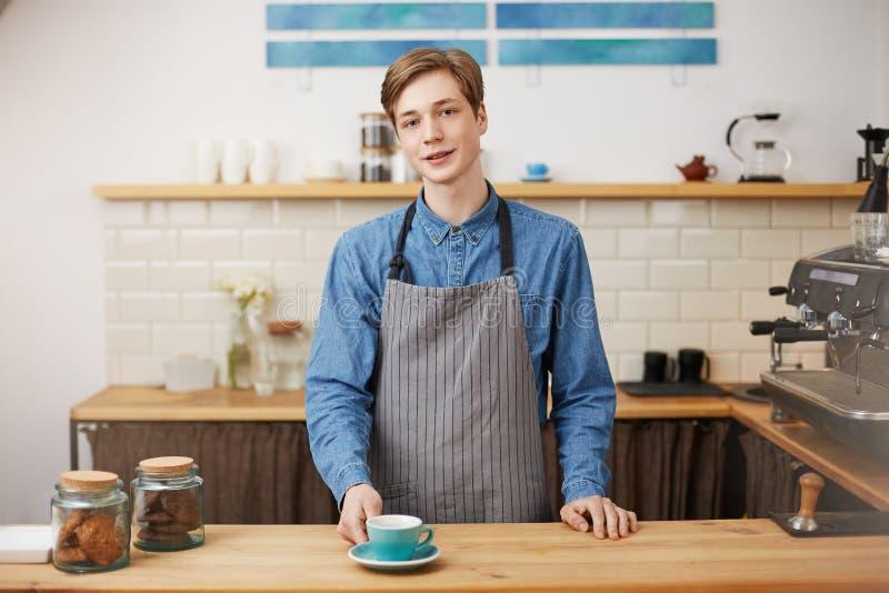 Gladlynt barista på stångräknaren Ge dräkt hans beställde coffe arkivfoto