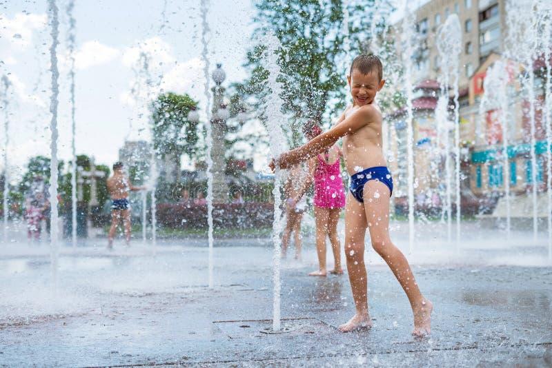 Gladlynt barn som spelar i en vattenspringbrunn och tycker om de kalla strömmarna av vatten i en varm dag för sommar fotografering för bildbyråer