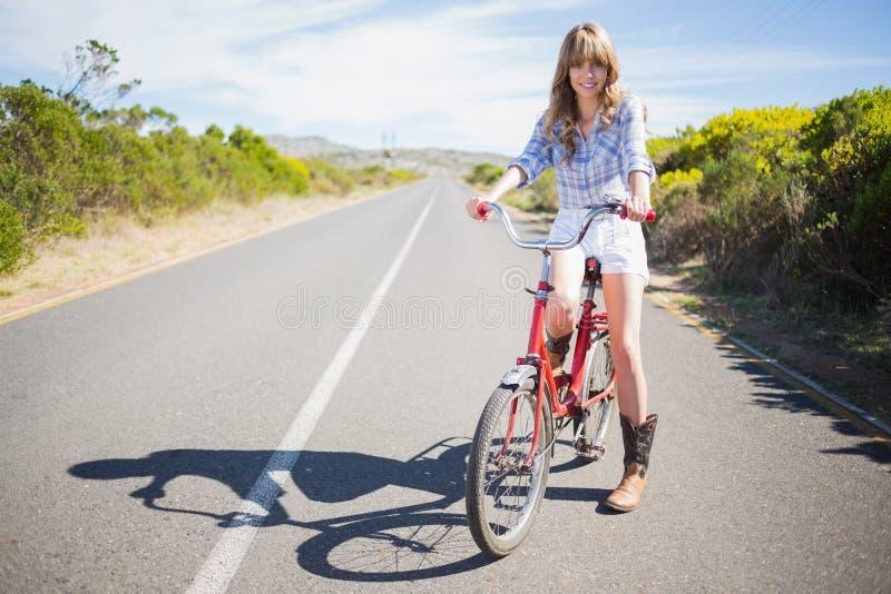 Gladlynt barnmodell som poserar, medan rida cykeln arkivbild