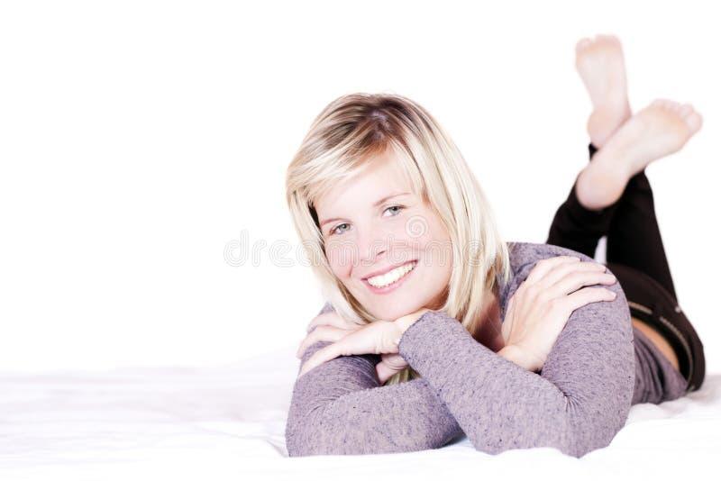 Gladlynt blond flicka i säng. arkivfoto