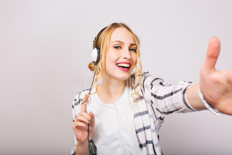 Gladlynt blond kvinna i den vita moderiktiga dräkten som poserar i stor hörlurar och att trycka på kameran och att skratta E fotografering för bildbyråer