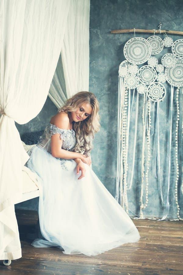 Gladlynt blond kvinna i ljust - blå aftonkappa i lyxig tappninginre arkivfoton