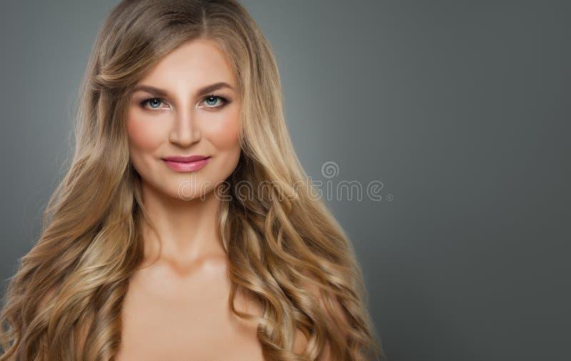 Gladlynt blond kvinna med den långa sunda lockiga frisyren och klar hud Håromsorg och cosmetologybegrepp royaltyfria foton