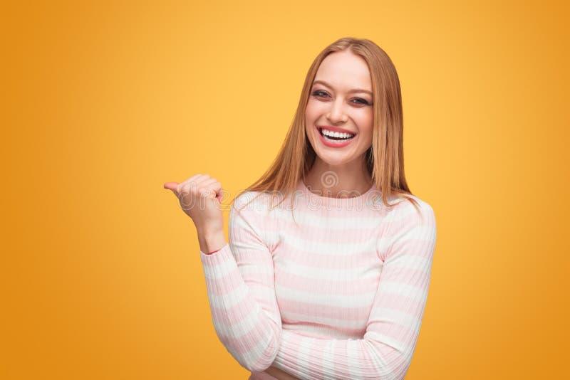 Gladlynt blond kvinna som bort pekar arkivfoton
